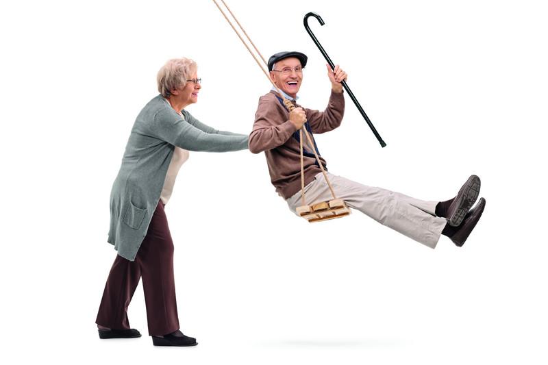 Elderly woman pushing a man on swing