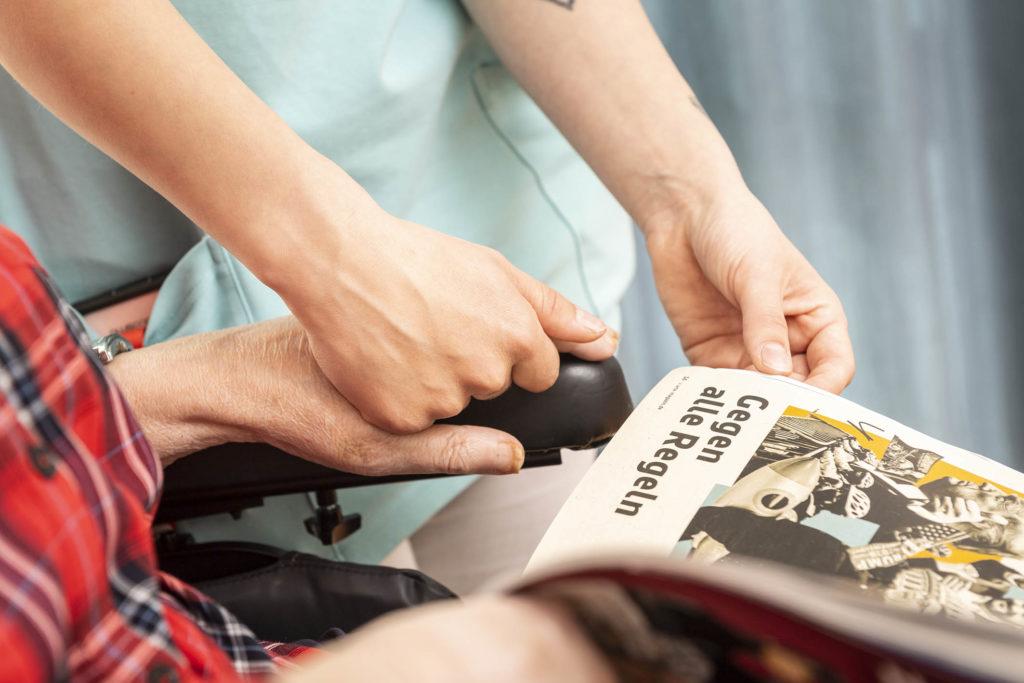Pflegerin hält Bewohnerin die Hand