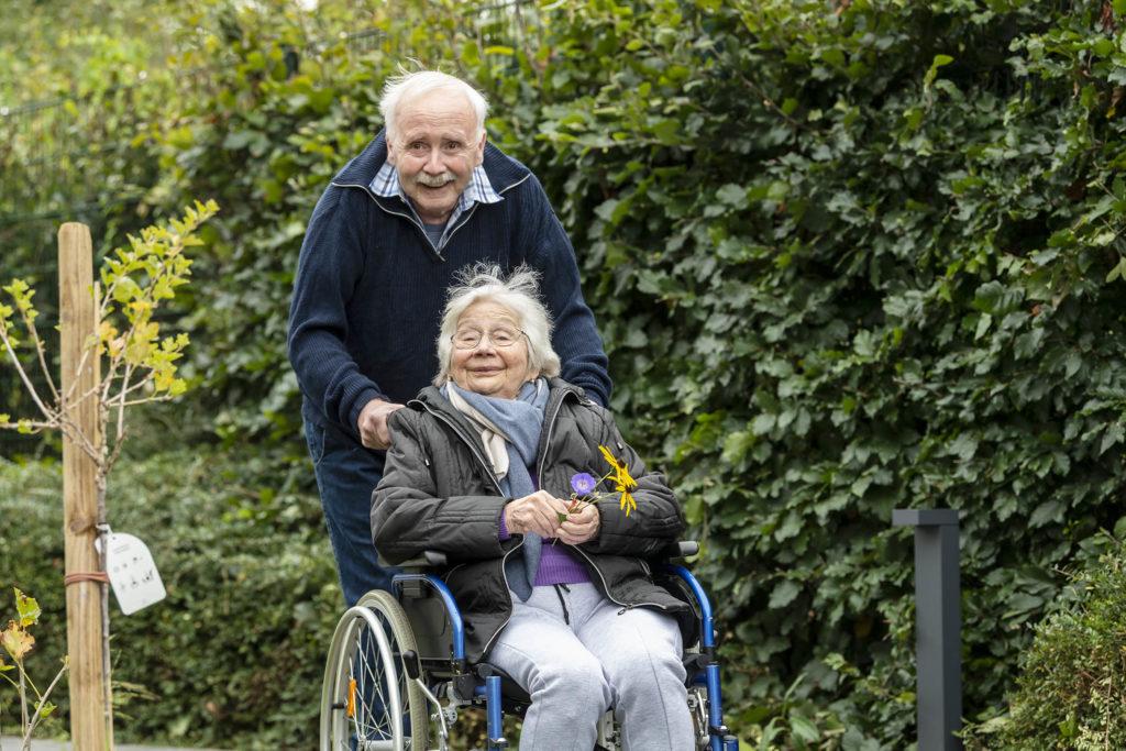 Ehemann schiebt seine Frau im Rollstuhl durch den Garten