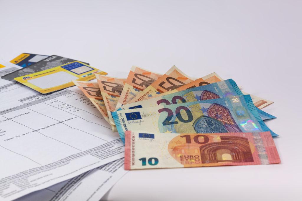 Geldscheine und Kreditkarten auf Kontoauszügen